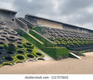 the seawall south of blackpool constructed of concrete honeycomb type structures with steps leading to the beach covered in tidal seaweed and dramatic grey sky