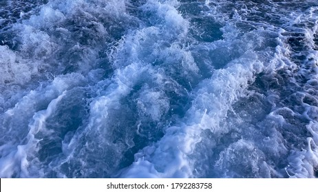 Seawater surface. White foam waves texture as a natural background.