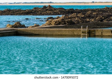 Seawater swimming pool at dusk in summer. Deep aqua or turquoise water and copy space. Granville, France.