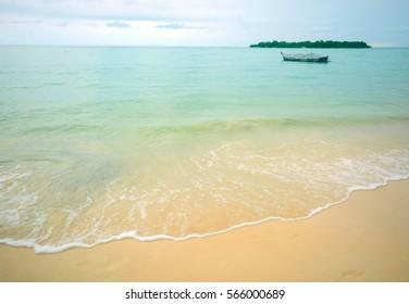 SEA-WAVE WHITE FOAM ON SANDY BEACH AT ISLAND SEASIDE