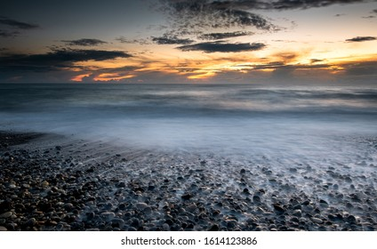 Seawaves splashing on the coast full of pebbles during a dramatic sunset. Paphos coast in Cyprus. Long exposure photography