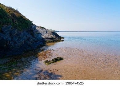 Seaweed lays nn the wet rippled sand, below the erroded slate cliffs of the River Dwyryd estary in Gywnedd, Wales