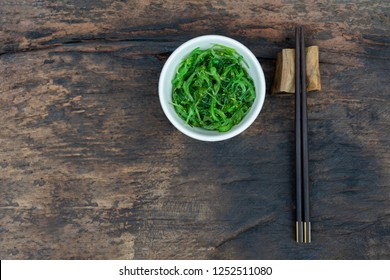 Seaweed salad or Chuka Wakame  in a bowl on wood background. Traditional Japanese food. Top view.
