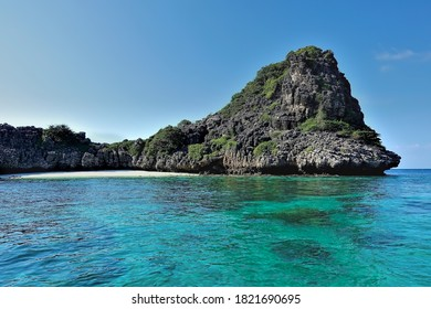 Secluded beach on the island. A semicircular strip of sand is surrounded by a rock. The clear aquamarine sea is calm. There are no people. Silence, relaxation. Thailand