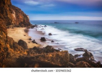 Secluded Pirateâ??s Cove Beach at sunset with a colorful sky and ocean water flowing around rock formations, Point Dume, Malibu, California