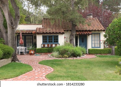Secluded cozy white stucco cottage with a terra cotta tiled roof.  The house has blue trimmed windows and doors, and a winding brick path with a lovely garden.  Old Monterey, CA.