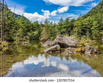 Secluded natural pond with boulders, with reflection of blue cloudy summer sky, in Japanese mountains, Kamikochi, Japan.