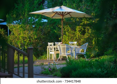 Secluded table with chairs and comfortable rattan chairs under a sunshade among green vegetation for a lovely dinner in the summer