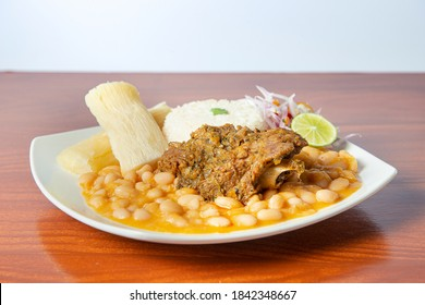 """""""Seco de cabrito"""", Peruvian food, consisting of a goat stew accompanied by beans. Wooden background."""