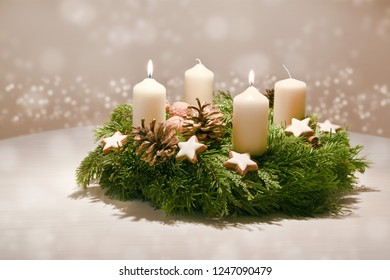 Second Advent - decorated Advent wreath from evergreen branches with white burning candles, tradition in the time before Christmas, warm background with festive bokeh and copy space, selected focus