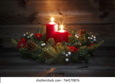 Second Advent - Decorated Advent wreath with two red burning candles on a wooden background with festive atmosphere