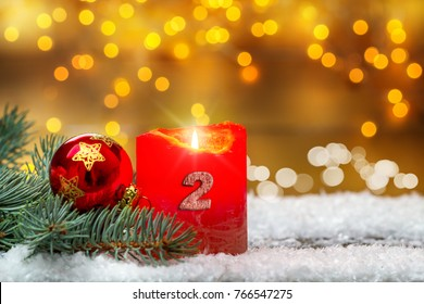Second advent, decorating with candle, ball and fir in the snow before Bokeh
