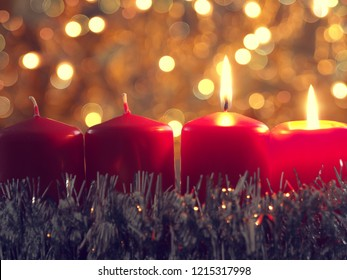 Second candle burning, seasonal background with red Advent candles and golden Christmas decoration