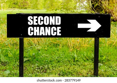 SECOND CHANCE written on directional black metal sign with arrow pointing to the right against natural green background. Concept image with available copy space