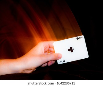 Second curtain flash sync photo with hand holding ace of clubs playing card.