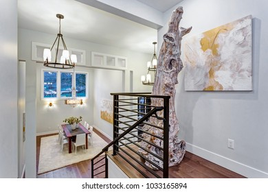 Second floor landing with white walls, maple hardwood floor and a driftwood statue next to an abstarct art piece on the wall.