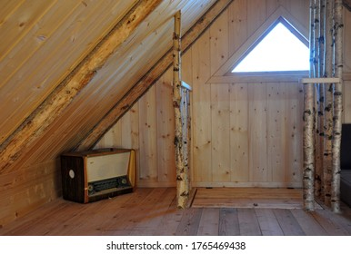 second floor under the roof wooden interior with a triangular window. old radio radiogramophone record player. solid birch railing. floor hatch to the stairs. wooden walls and ceiling