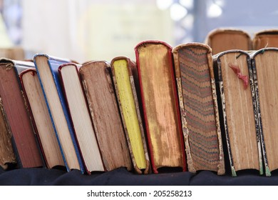 Second hand books leaning against each other for sale in a street book market