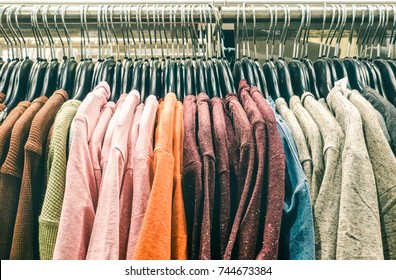 Second hand pullover clothes hanging on shop thrift at flea market store - Hipster wardrobe sale concept and alternative retro moda fashion styling - Soft contrast desaturated nostalgic filtered look