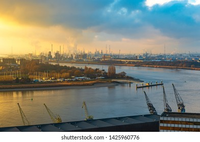 The second largest industrial harbor of Europe at sunset with cranes in the foreground, chemical and nuclear plants in the background and the Scheldt River, Antwerp, Belgium.