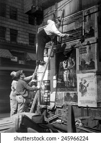 Second Liberty Loan Campaign during WWI. Movie star Fattie Arbuckle, balanced on a ladder, putting up a Liberty Loan poster at Times Square, New York. Oct. 1917.