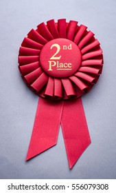 Second place red winners rosette on grey with gold text and ribbon conceptual of winning and achievement in a competition