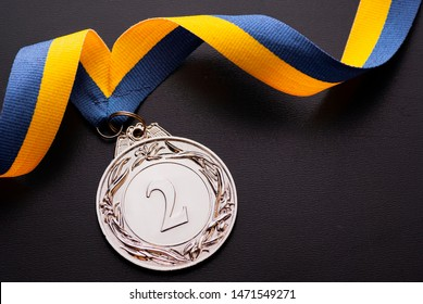 Second place runner-up silver medal on a twirled blue and gold ribbon over a dark grey background with copy space viewed from above