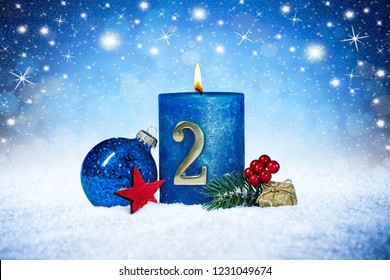 second sunday of advent blue candle with golden metal number red decoration one on wooden planks in snow front of silver panorama bokeh background