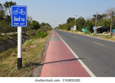 "Secondary route with a sign in Thai ""keep left"""