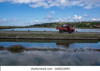 Secovlje Saltworks, Piran / SLOVENIA - September 9, 2019: Way between water lakes, speed blurry car with workers in saltworks in cloudy weather