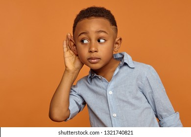 Secrecy and confidential information concept. Portrait of funny curious African schoolboy eavesdropping, touching ear and looking away with surprised interested facial expression, posing in studio
