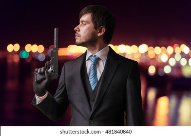Secret agent or assassin is holding gun with silencer in hand at night.