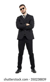 Secret agent or bodyguard with crossed arms looking at camera. Full body length portrait isolated over white studio background.