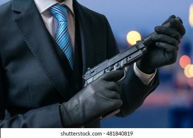 Secret agent holds pistol with silencer in hands at twilight.