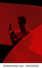 Secret Agent Spy Silhouette in Light Painting  Backdrop - Retro tough Woman with Gun in Red Lights Composition