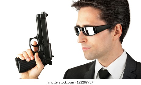 Secret Agent. With sunglasses and gun in front of white background