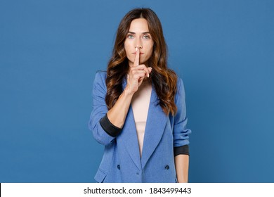 Secret attractive young brunette woman 20s wearing basic jacket standing saying hush be quiet with finger on lips shhh gesture looking camera isolated on bright blue colour background studio portrait