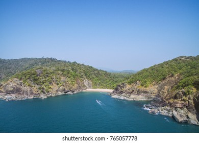 Secret beach Butterfly in Goa, India. Aerial view of pristine beach with rocky bay and waves crashing