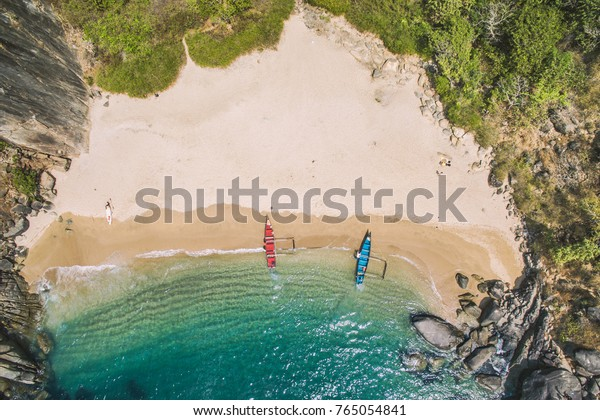 Secret beach Butterfly in Goa, India. Aerial view to pristine beach with rocky bay and waves crashing