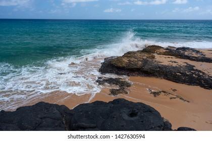 Secret Beach On Kauai With Black Lava Rocks and waves