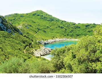 Secret blue cove bay surrounded by green hills and bushes near the beach