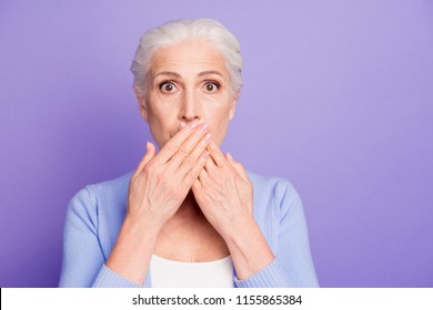Secret concept. Portrait of beautiful nice shocked gray-haired old lady wearing casual, covering her mouth with palms. Copy space.  Isolated over pastel violet purple background