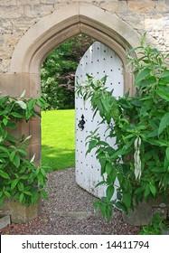 Secret Garden, sunlight lies beyond ancient garden wall and Arched Door