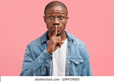Secret gesture. Portrait of attractive dark skinned African American male shows silence sign, asks to keep private information confidential, has surprised expression, isolated over pink background.