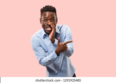 Secret, gossip concept. Young afro man whispering a secret behind his hand. Businessman isolated on trendy pink studio background. Young emotional man. Human emotions, facial expression concept.