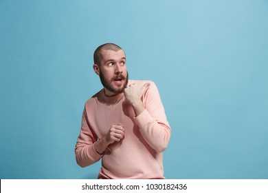 Secret, gossip concept. Young man whispering a secret behind her hand. Business man isolated on trendy blue studio background. Young emotional man. Human emotions, facial expression concept.