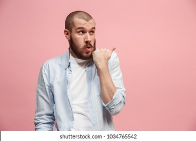 Secret, gossip concept. Young man whispering a secret behind her hand. Business man isolated on trendy pink studio background. Young emotional man. Human emotions, facial expression concept.