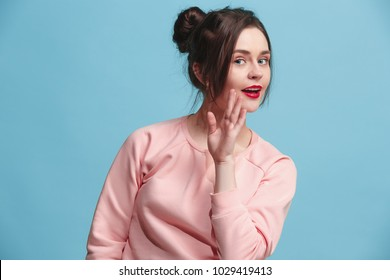 Secret, gossip concept. Young woman whispering a secret behind her hand. Business woman isolated on trendy blue studio background. Young emotional woman. Human emotions, facial expression concept.