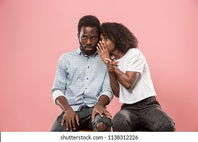 Secret, gossip concept. Young woman whispering a secret behind her hand to afro man. African couple isolated on trendy pink studio background. Young emotional afro woman and man. Human emotions