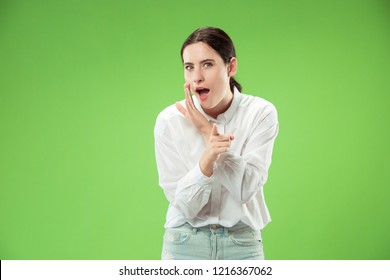 Secret, gossip concept. Young woman whispering a secret behind her hand. Business woman isolated on trendy green studio background. Young emotional woman. Human emotions, facial expression concept.